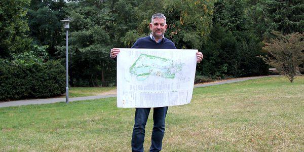 Ratsherr Torsten Röpke zeigt den Plan für die Sanierung des Stadtparkes